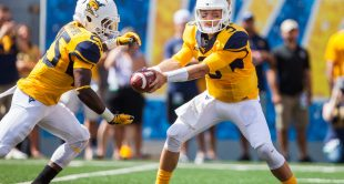 West Virginia Mountaineers quarterback Skyler Howard (3) hands the ball to Justin Crawford (25) during the first quarter against the Missouri Tigers at Milan Puskar Stadium.