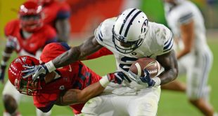 Brigham Young running back Jamaal Williams (21) stiff-arms an Arizona tackler during the Cougars' 18-16 win in Phoenix.