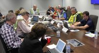 Drill participants discuss their plan for restoring electric service in a scenario where high winds and heavy rain caused power outages for nearly 300,000 people. Appalachian Power's storm leadership team members wear vests that identify their storm response roles.