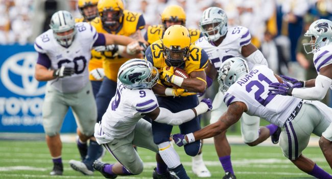 West Virginia Mountaineers running back Justin Crawford (25) runs the ball and is tackled by Kansas State Wildcats linebacker Elijah Lee (9) during the second quarter at Milan Puskar Stadium