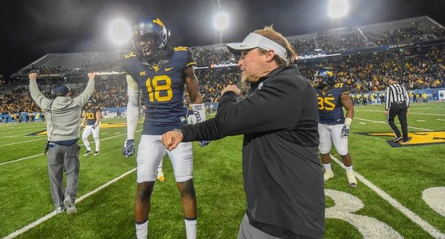 Safety Marvin Gross (18) celebrates the game-clinching turnover with coach Dana Holgorsen near the end of West Virginia's 24-21 win over Baylor.