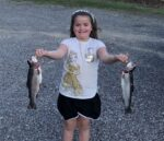 Maci Kessler, age 8, with a couple of really nice rainbow trout caught while fishing with her grandpa Joe Kessler of Milton, W.Va.