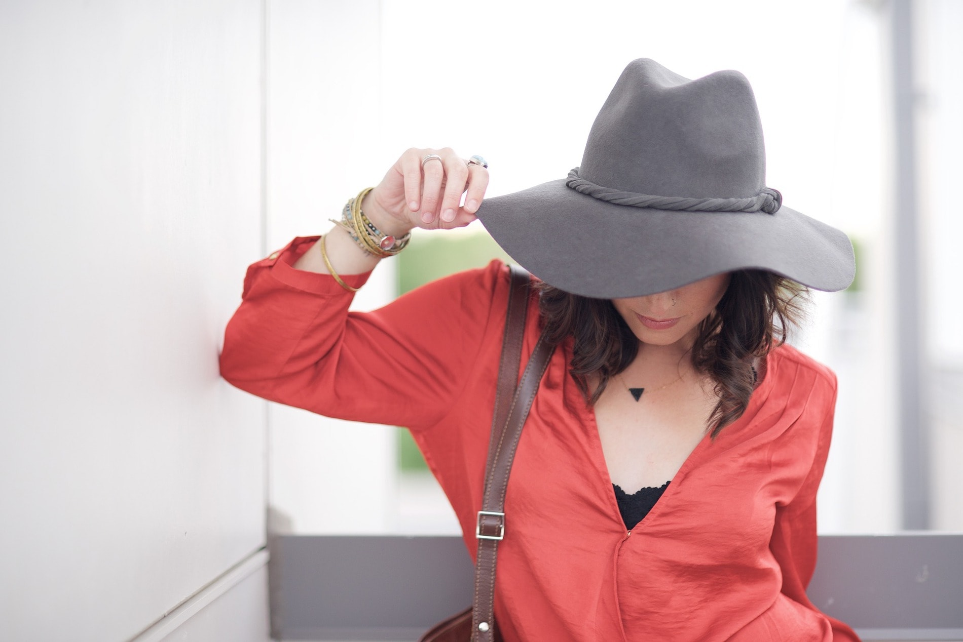 Model looking down wearing a red dress and wide-brimmed hat