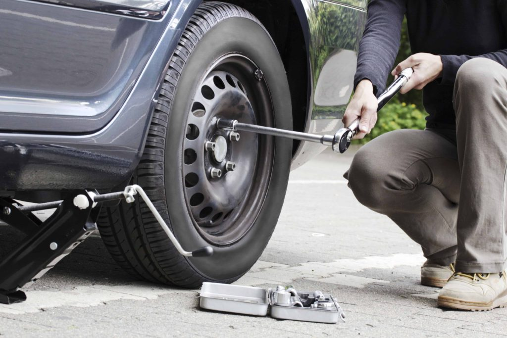 Women changing a tire with a torque wrench