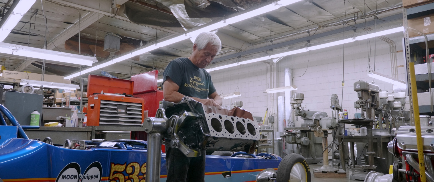 Chico Kodama working on engine at US Mooneyes garage