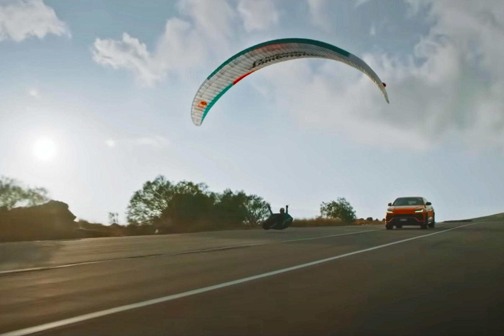 Lamborghini Urus and paraglider on pavement