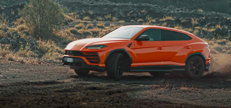 orange Lamborghini Urus sliding in dirt