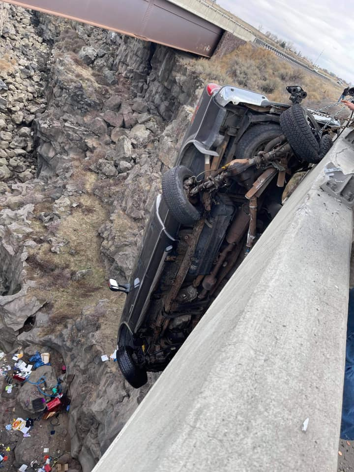 truck dangles from bridge by trailer safety chain