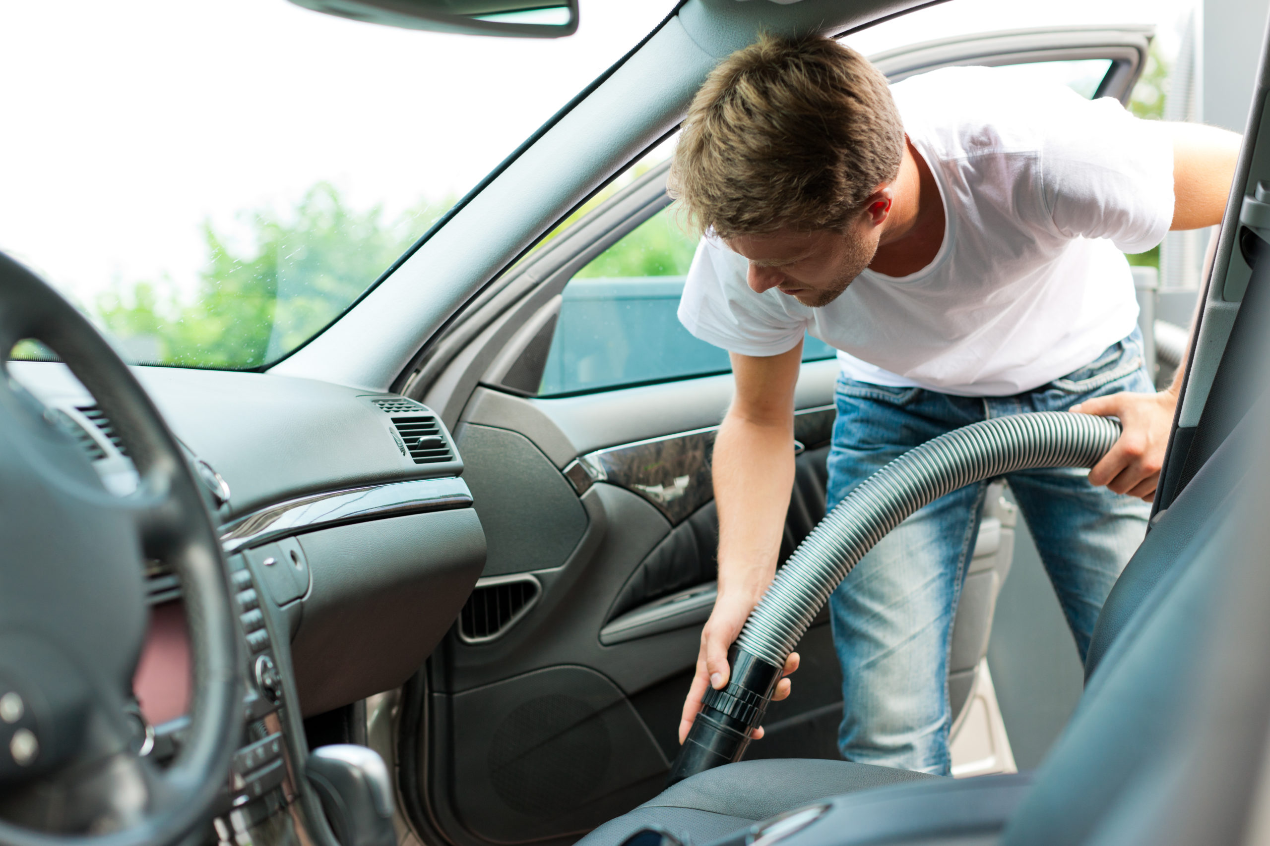 how to detail your car - man vacuums interior of car