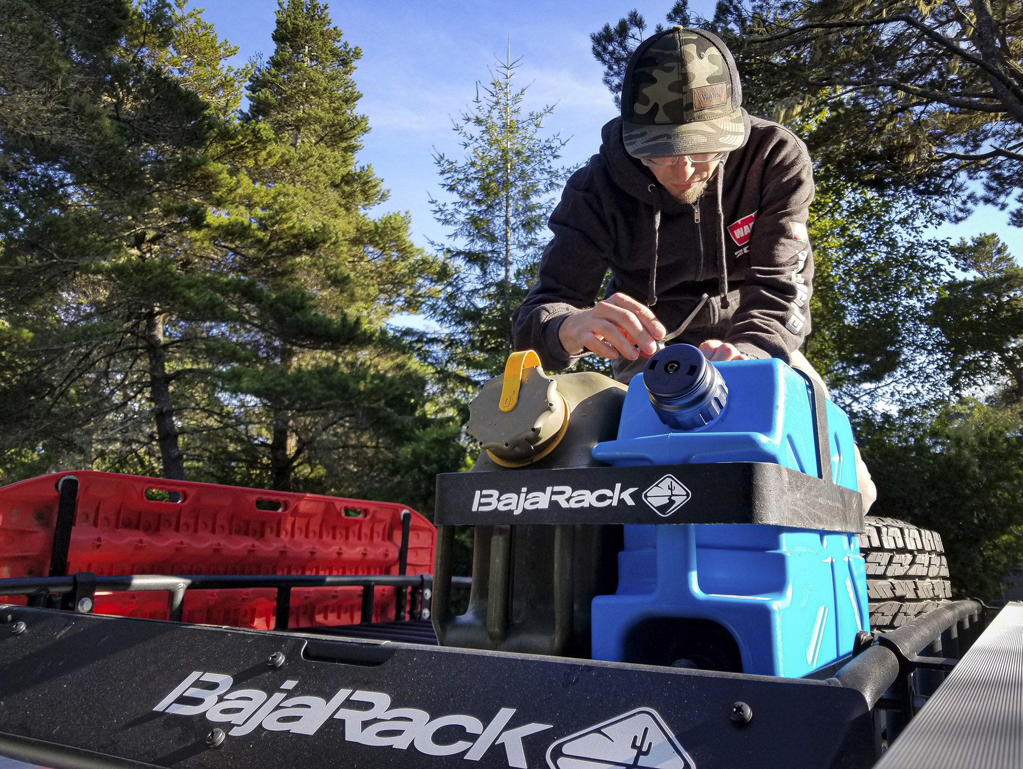 BajaRack roof basket holds red MATRAX recovery boards, a blue water jerry can, and army green diesel fuel can.