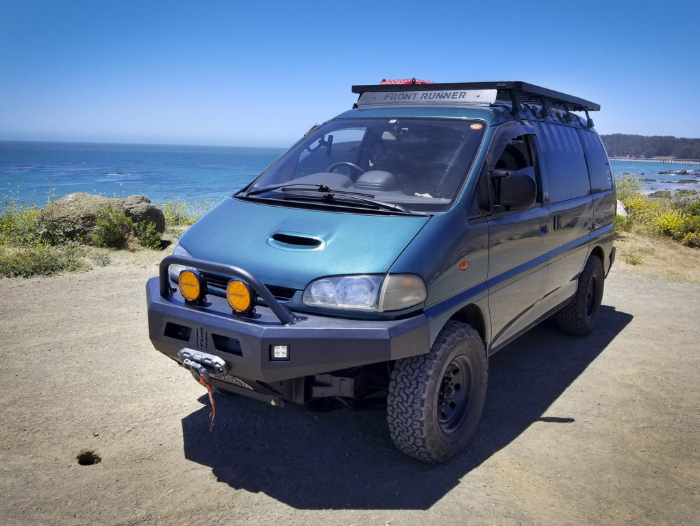 A black Front Runner platform roof rack sits on a teal-colored Mitsubishi Delica Space Gear
