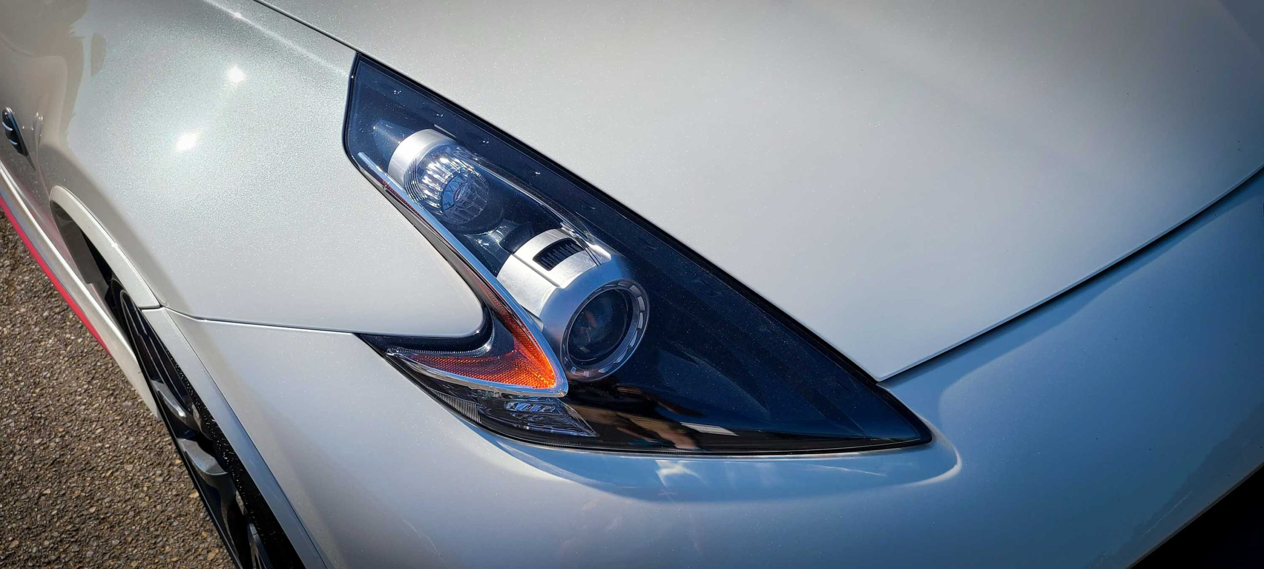 The white Nissan 370Z Nismo's headlights are oversized and sleek.
