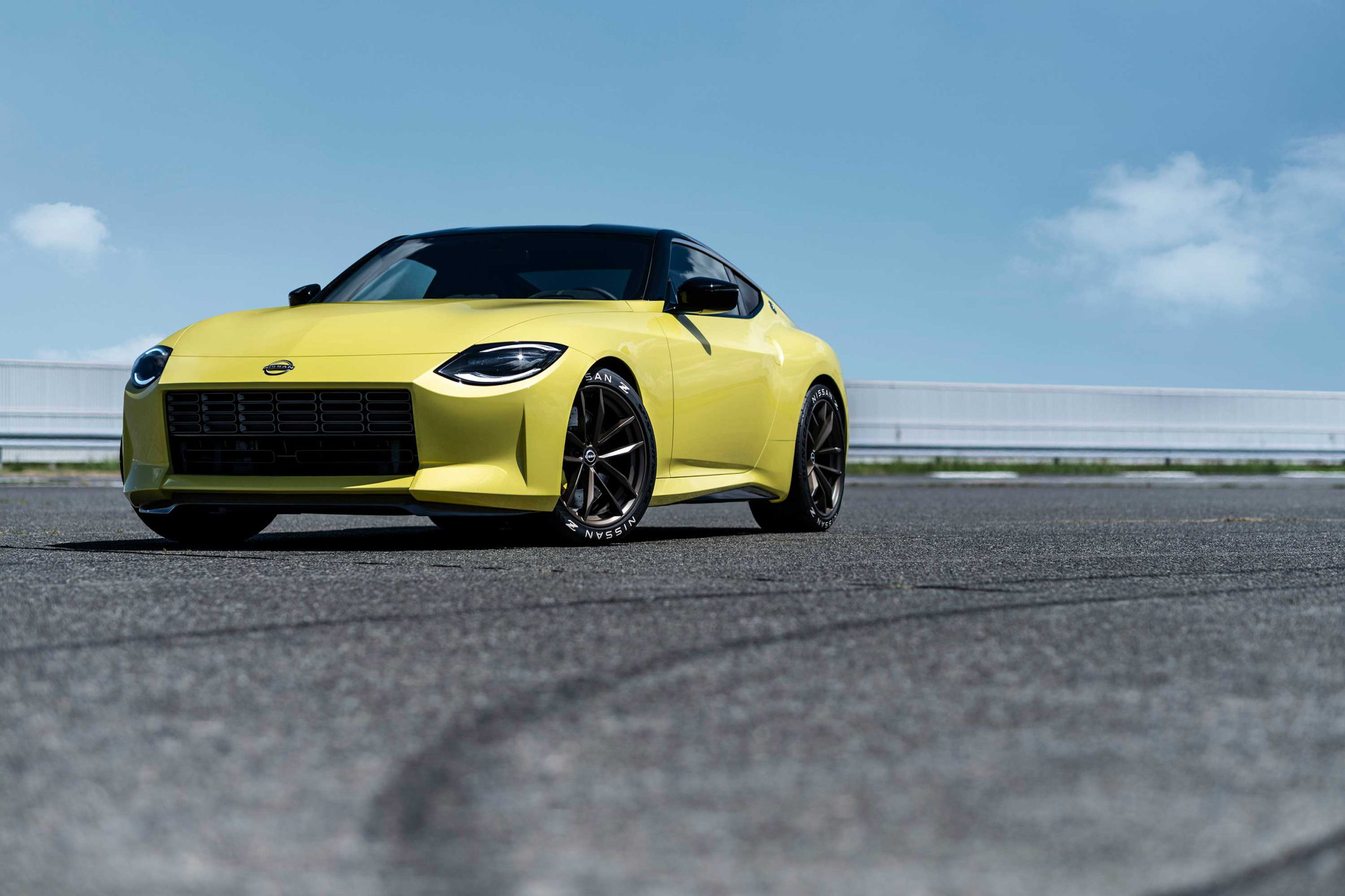 The Nissan 400Z prototype with yellow exterior sits on a paved track with tire marks.