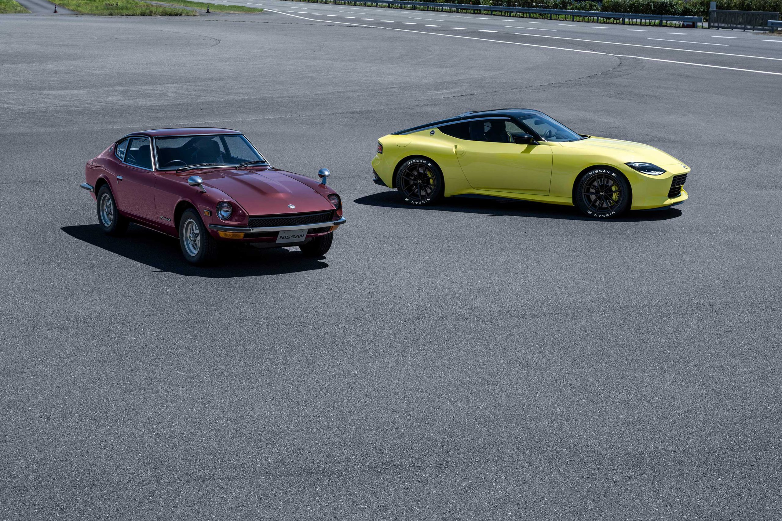 Nissan 400Z Prototype with yellow exterior next to maroon heritage car.