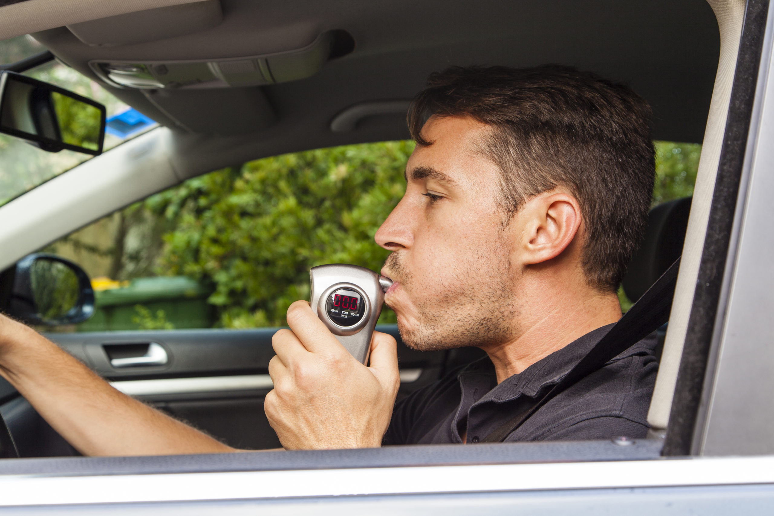 man sitting in car blows into breathalyzer - infrastructure bill aims to reduce drunk driving
