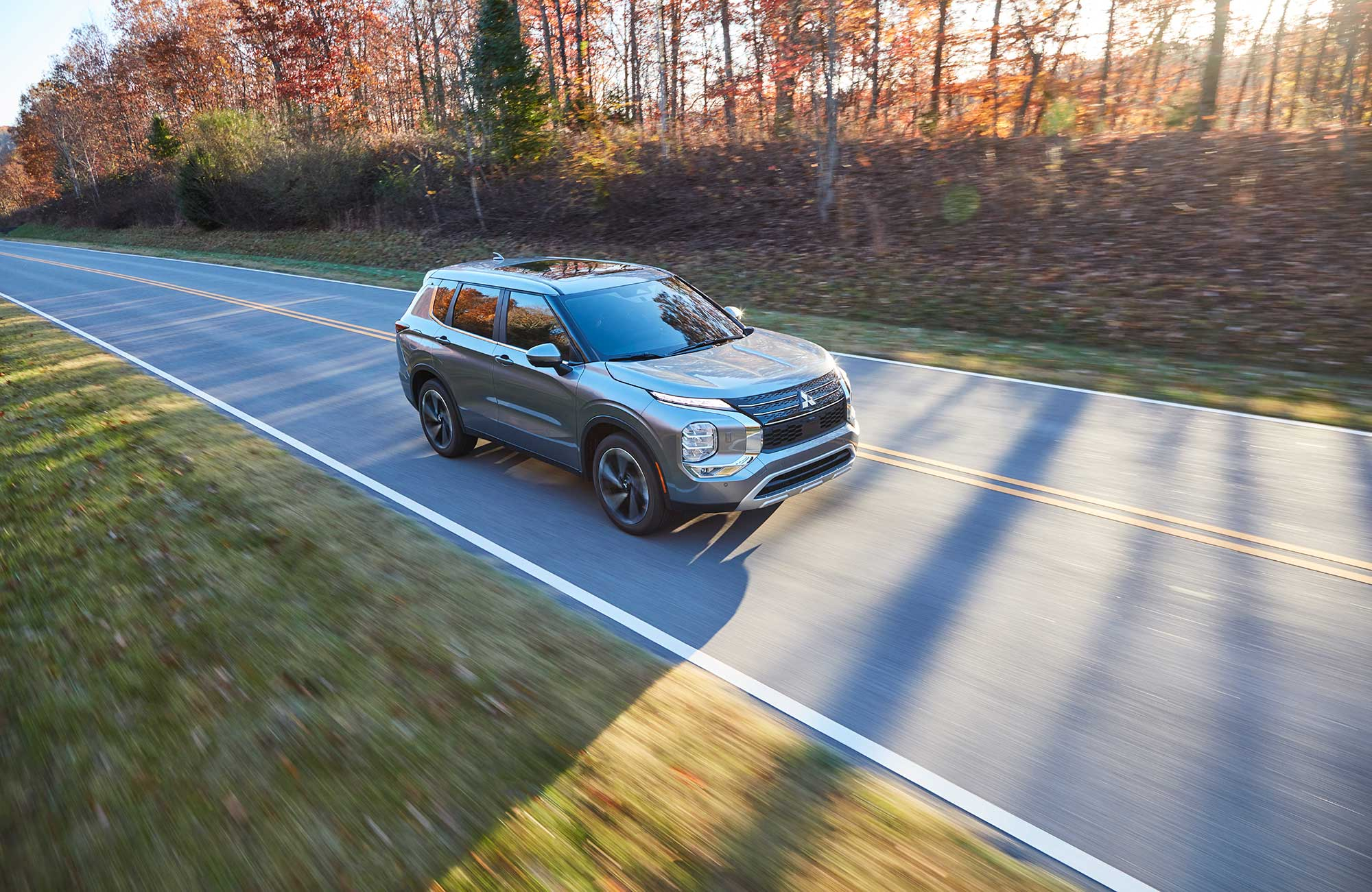 The 2022 Mitsubishi Outlander driving on a road.