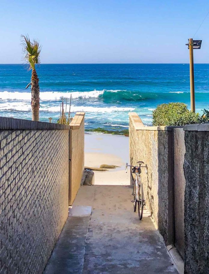 bikerumor pic of the day a bicycle leans against a brick wall hallway that leads to the ocean in Late Feb in La Jolla California the ocean is bright blue with a cloudless sky.
