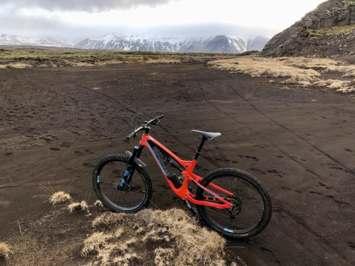 a red mountain bike is in a field of lava rock sand with tall snow capped mountains in the distance in iceland