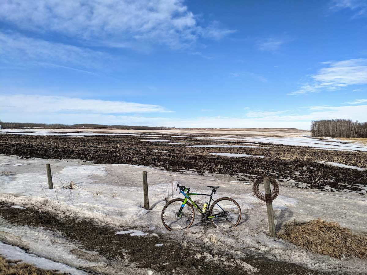 bikerumor pic of the day Sturgeon County, Alberta, bike leaning against a barbed wire fence with snow covering the side of the road and muddy field in the background the sky is blue with some whispy clouts.