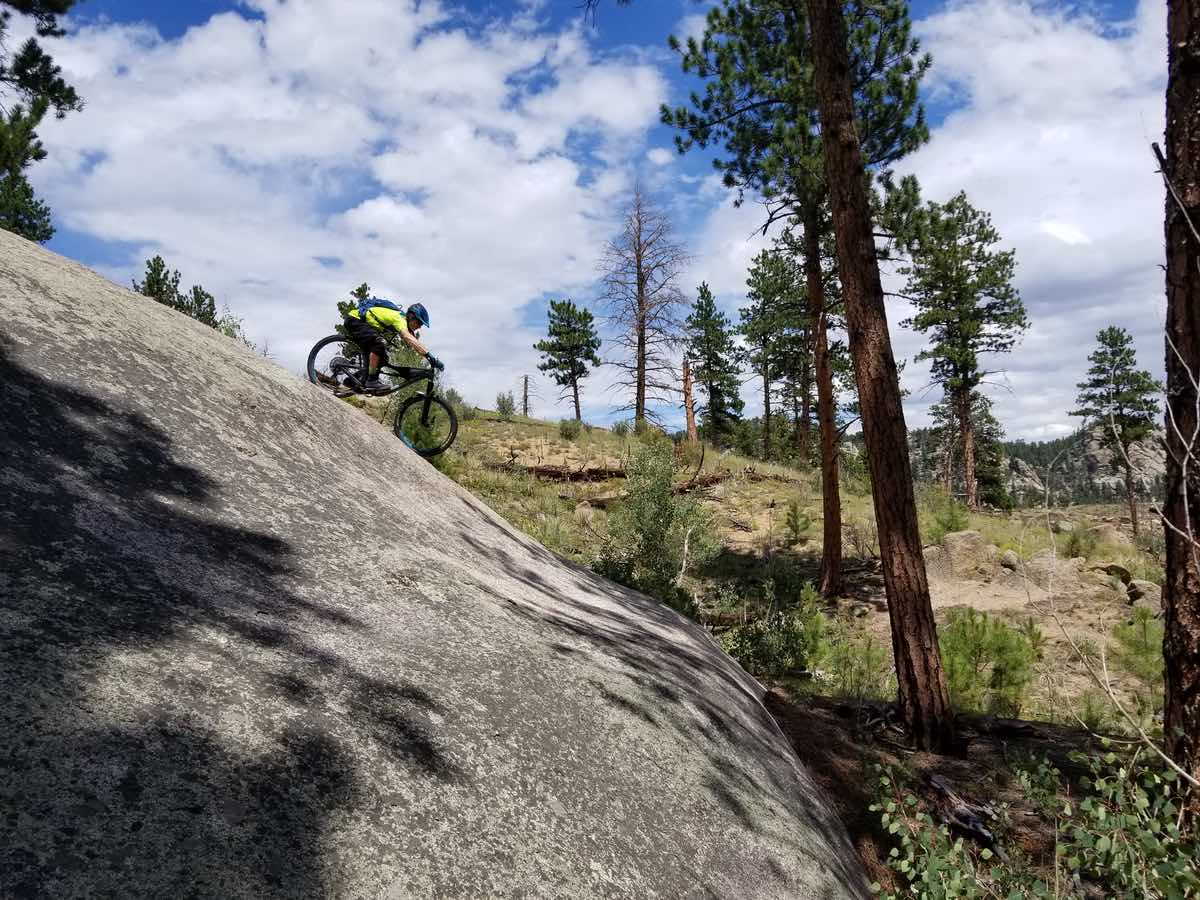 bikerumor pic of the day buffalo creek trails in colorado a mountain biker leans far back on their bike as they ride down a smooth steep rock there are pine trees in the background and the blue sky is dotted with clouds.