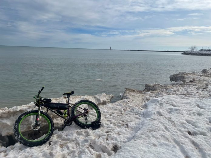 bikerumor pic of the day fat biking on lake michigan, snow and ice on the edge of the lake as a fat bike lays in the snow. the sky is large and mostly covered in clouds