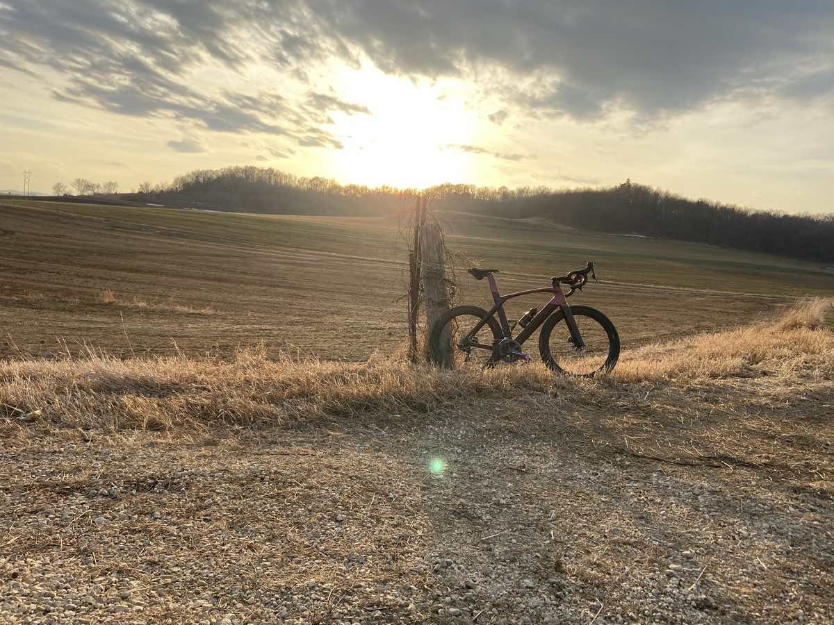 bikerumor pic of the day a road bike leans against an old broken wood pole outside of lacrosse wisconsin surrounded by brown grassy fields with the evening sun setting above a ridge in the distance the sun makes everything look gold.