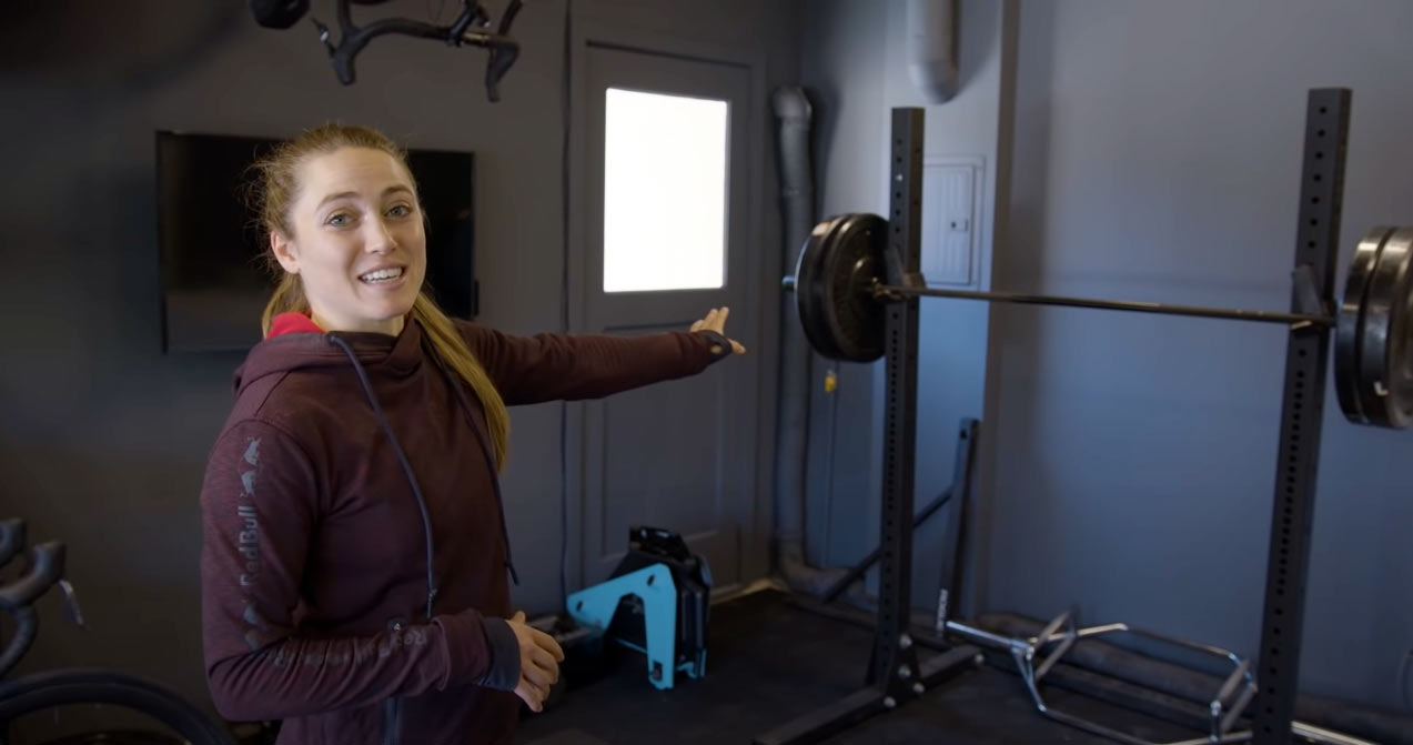 kate courtney in her home gym next to squat rack