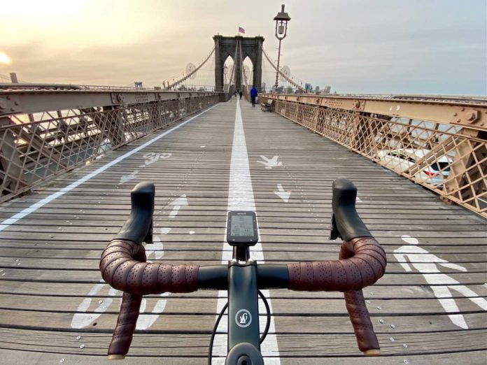 bikerumor pic of the day a photo of the handlebars of a bicycle positioned in the center of the brooklyn bridge in new york city at dusk.