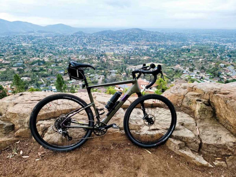 bikerumor pic of the day a bicycle is perched atop a dirt and rocky mountain top above a city on mount helix california.