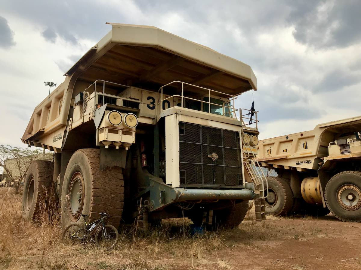 bikerumor pic of the day a bicycle leans agains the giant tire of a decommissioned dump truck in tanzania