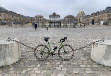 bikerumor pic of the day a ratchet outback bicycle leans against a chain fence on a cobblestone square leading to the Palace of Versailles in paris france. the gates are closed and there are only a handful of people walking around the square on an overcast day