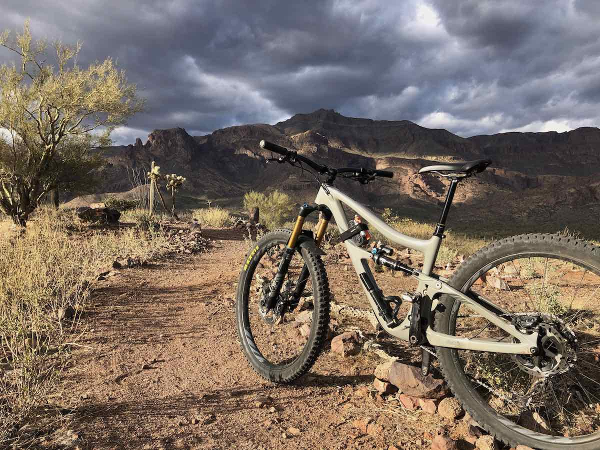 bikerumor pic of the day mountain bike at the Superstition mountain foothills near Phoenix arizona a full suspension mountain bike is perched on the edge of a rocky trail with scrub brush and mountain in the distance sun is peeking through the heavy clouds in the sky
