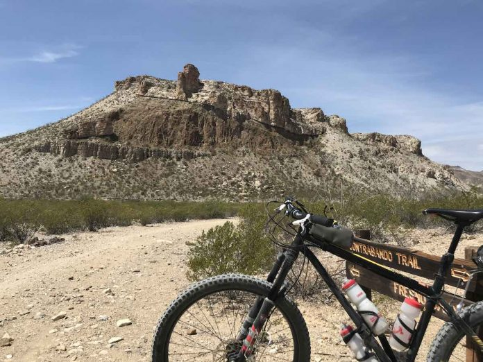 mountain bike next to a trail sign in beg bend ranch state park texas by a dirt trail with a rocky mountain in the distance