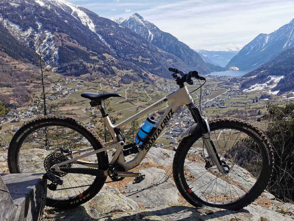 bikerumor pic of the day Val Poschiavo in Switzerland, a mountain bike is on a silk rock outcropping with snow capped alps in the far distance
