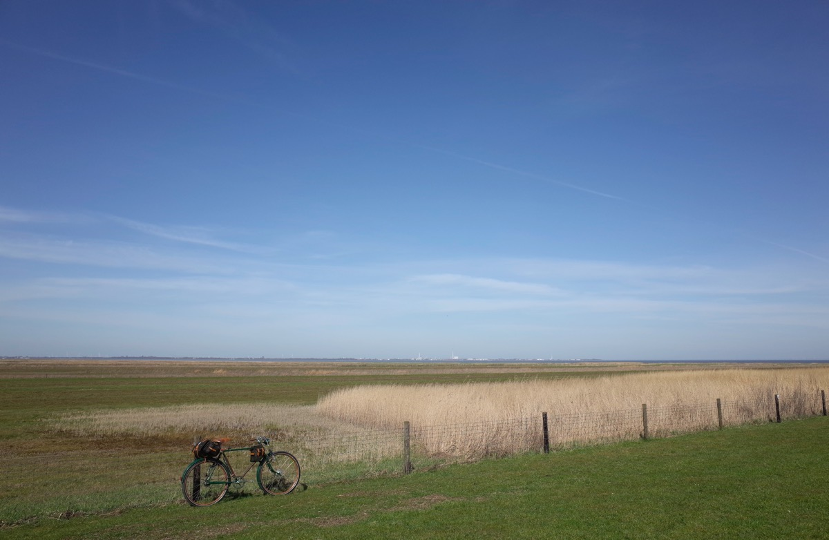 bikerumor pic of the day a Göricke touring bicycle leans against a wire fence in a green field bordered with golden wheat and great big blue skies. a small town can be seen on the horizon.