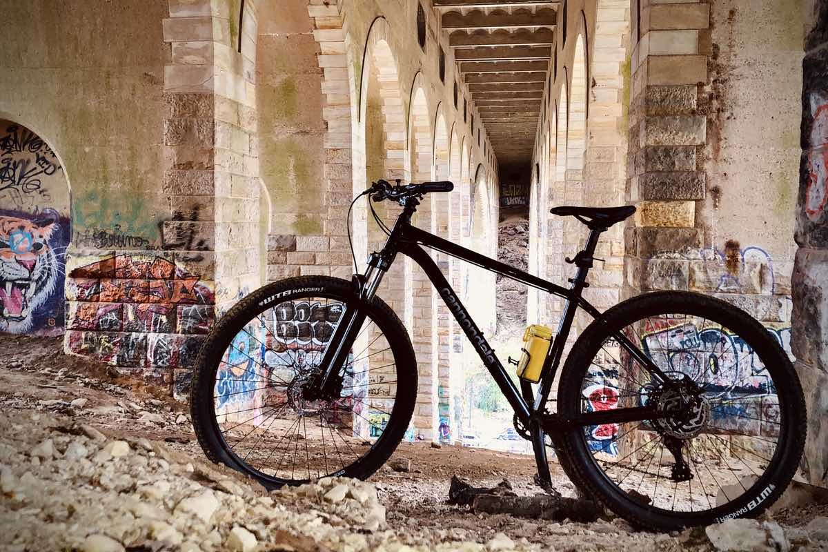 bikerumor pic of the day a bicycle is posed under a bridge that has graffiti spray painted on it.