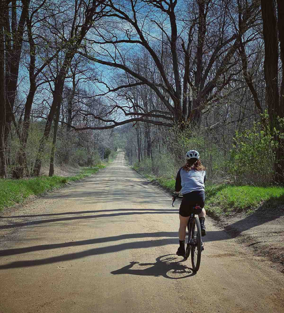 a bicyclist rides on a packed dirt road facing away from the camera. There are trees on either side of the road that are just beginning to leaf out and grass is very green on the edges.