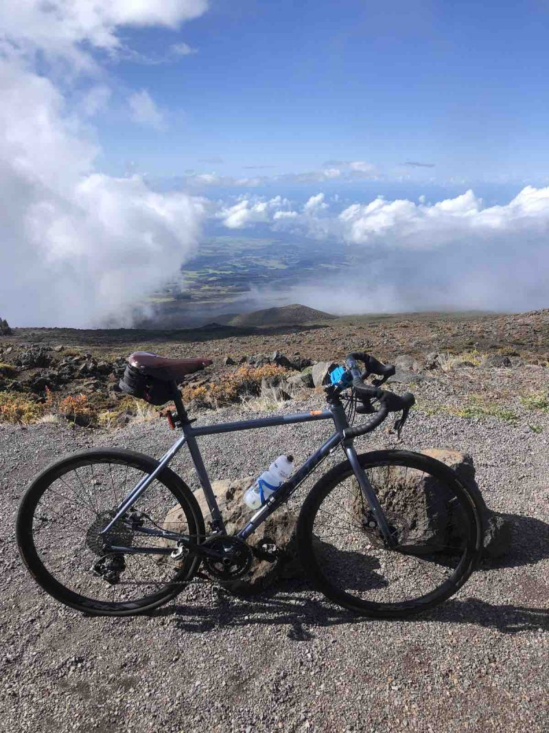 a bicycle is leaning against a rock a the top of haleakala in hawaii. The view looks out over the island through the clouds.