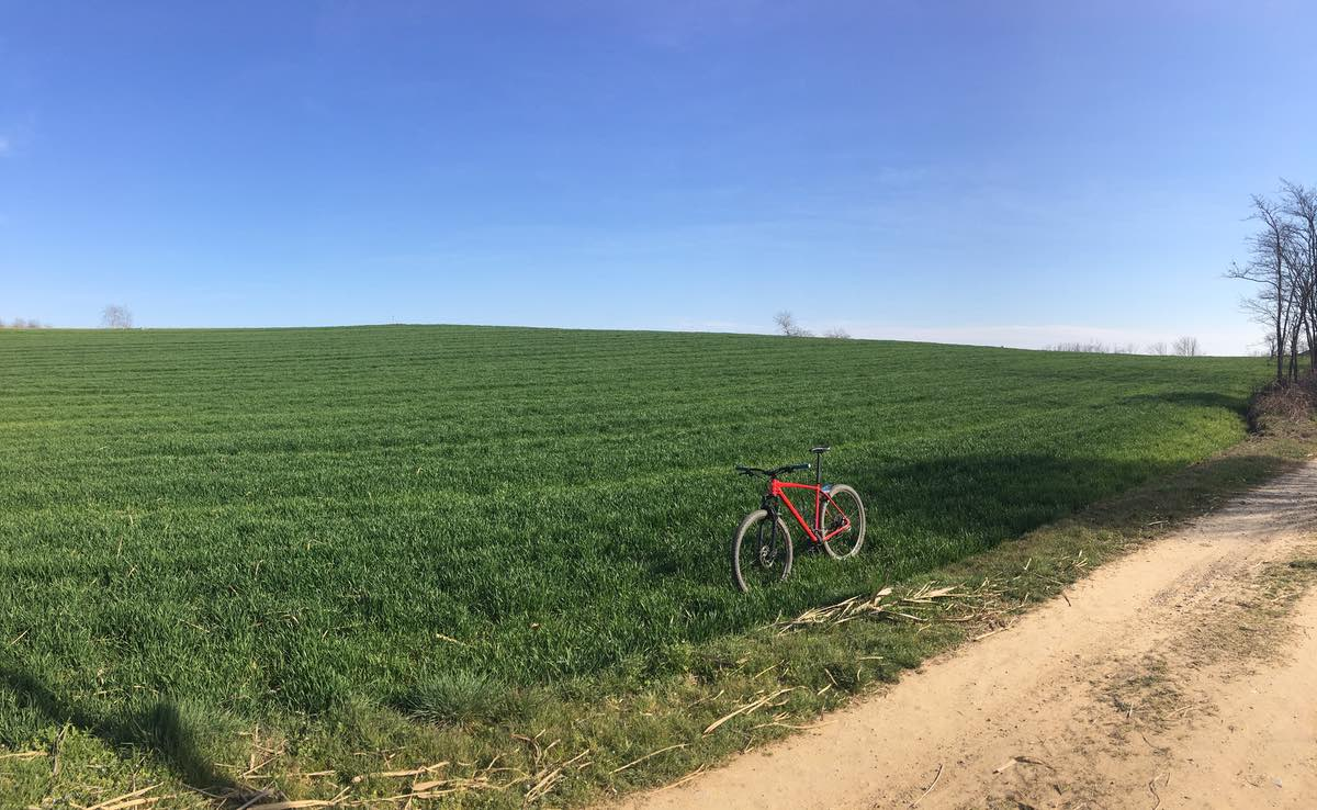 bikerumor pic of the day a large green grassy field with a dirt road to the right of the photo. A red bicycle is on the edge of the field and the sky is clear and blue.
