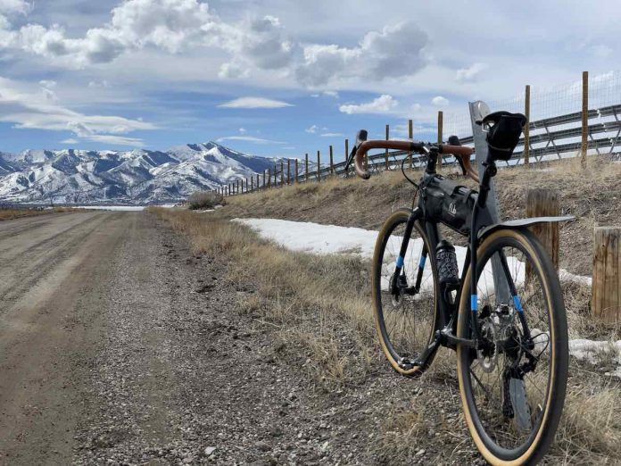 bikerumor pic of the day a gravel bike is in the right of the photo facing towards snow capped mountains in the distance. there is a wood fence bordering the gravel road and fluffy white clouds in the sky.