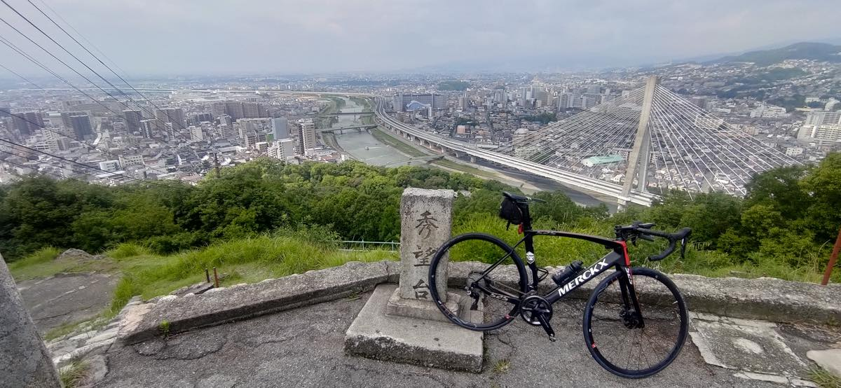 bikerumor pic of the day Ikeda city, Osaka, a bicycle is posed near a stone marker at the top of a mountain overlooking a city with hazy mountains in the distance.