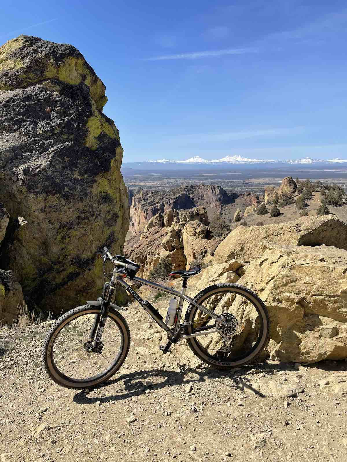 bikerumor pic of the day a mountain bike is posed near a large rock with another larger rock formation to the left of the photo snow capped mountains can be seen in the distance with clear blue skies.
