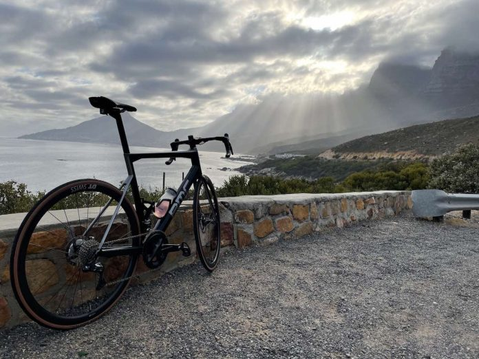 bikerumor pic of the day a bcc road bike leans against a low rock wall overlooking a bay surrounded by mountains the sky is cloudy and the sun is shining through with rays spreading out in the distance