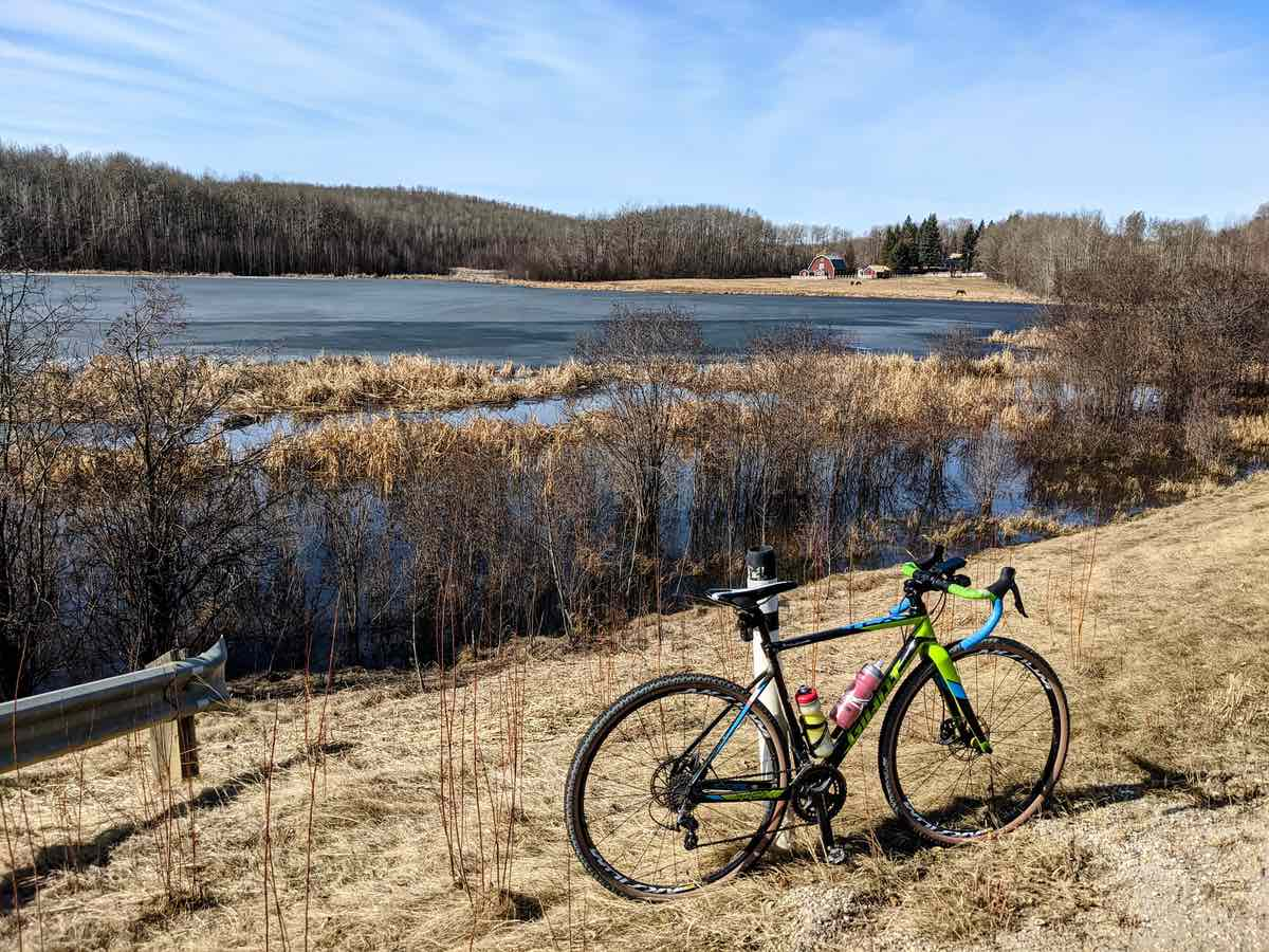 bikerumor pic of the day a gravel bike is positioned in a golden grass area near a lake - across the lake there is a barn. the day is bright and there are whips clouds in the sky.