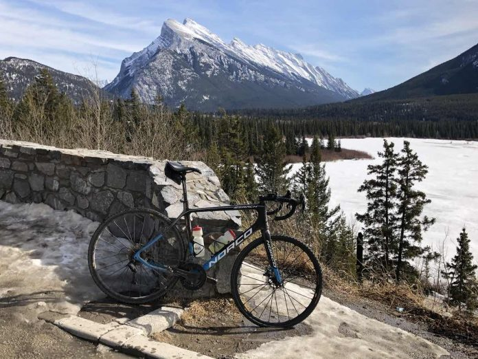 bikerumor pic of the day a bicycle leans against a low stone wall with a lake surrounded by pine trees and a snow capped mountain in the distance.