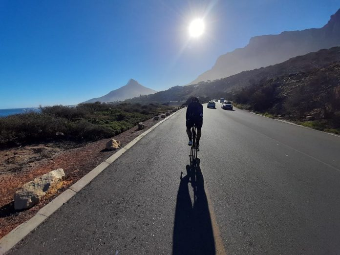 bikerumor pic of the day a cyclist is riding on a paved road away from the camera towards the sun that is low in the blue sky and some mountain peaks in the distance.
