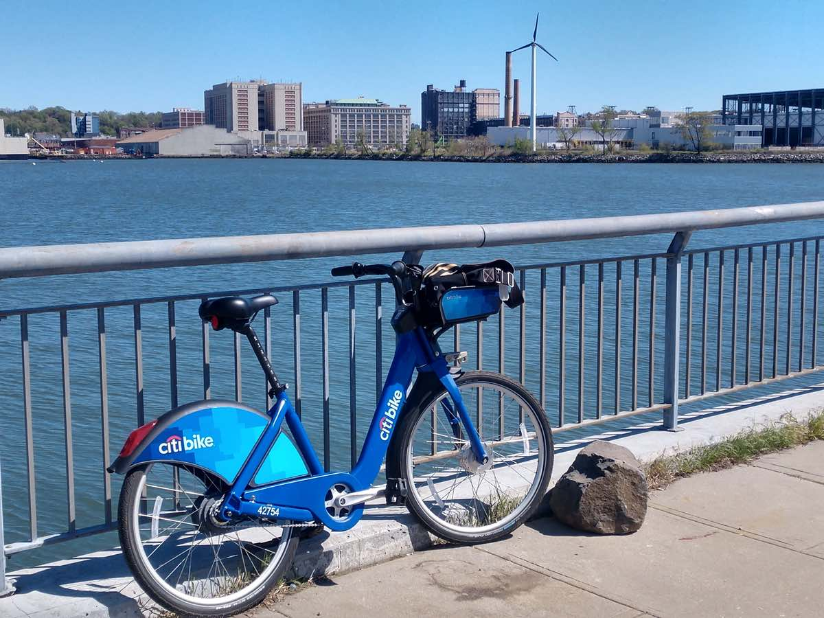 bikerumor pic of the day a citibike leans against a railing along a path overlooking city buildings and a wind turbine in brooklyn new york.