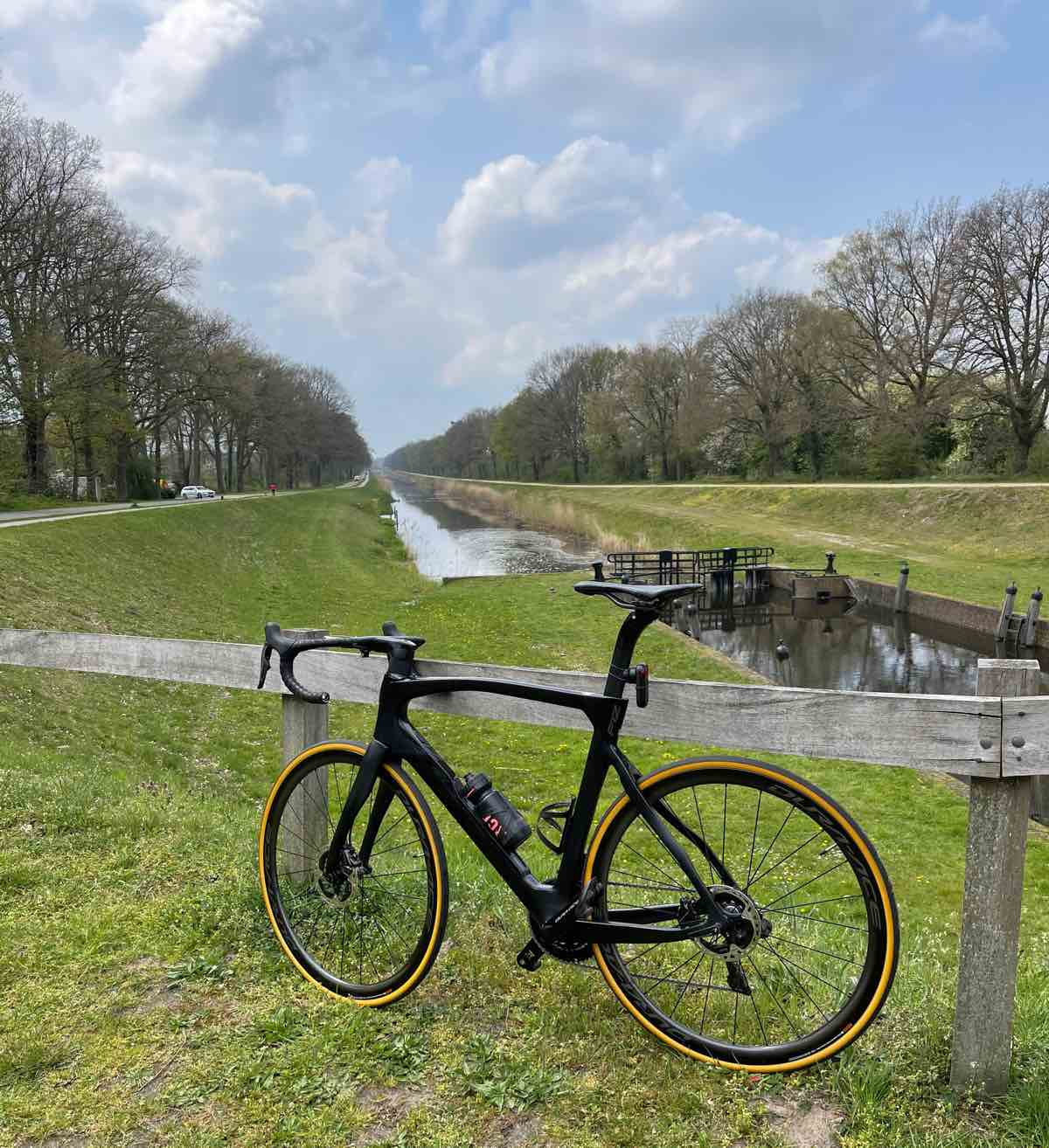 bikerumor pic of the day a road bicycle leans against a wooden fence near a cycle path that follows a canal there are trees bordering the sites of the canal.