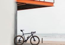bikerumor pic of the day a bicycle leans against a wall under an orange steel platform at the sea. the sea is grey and the sky looks very white and cloudy.