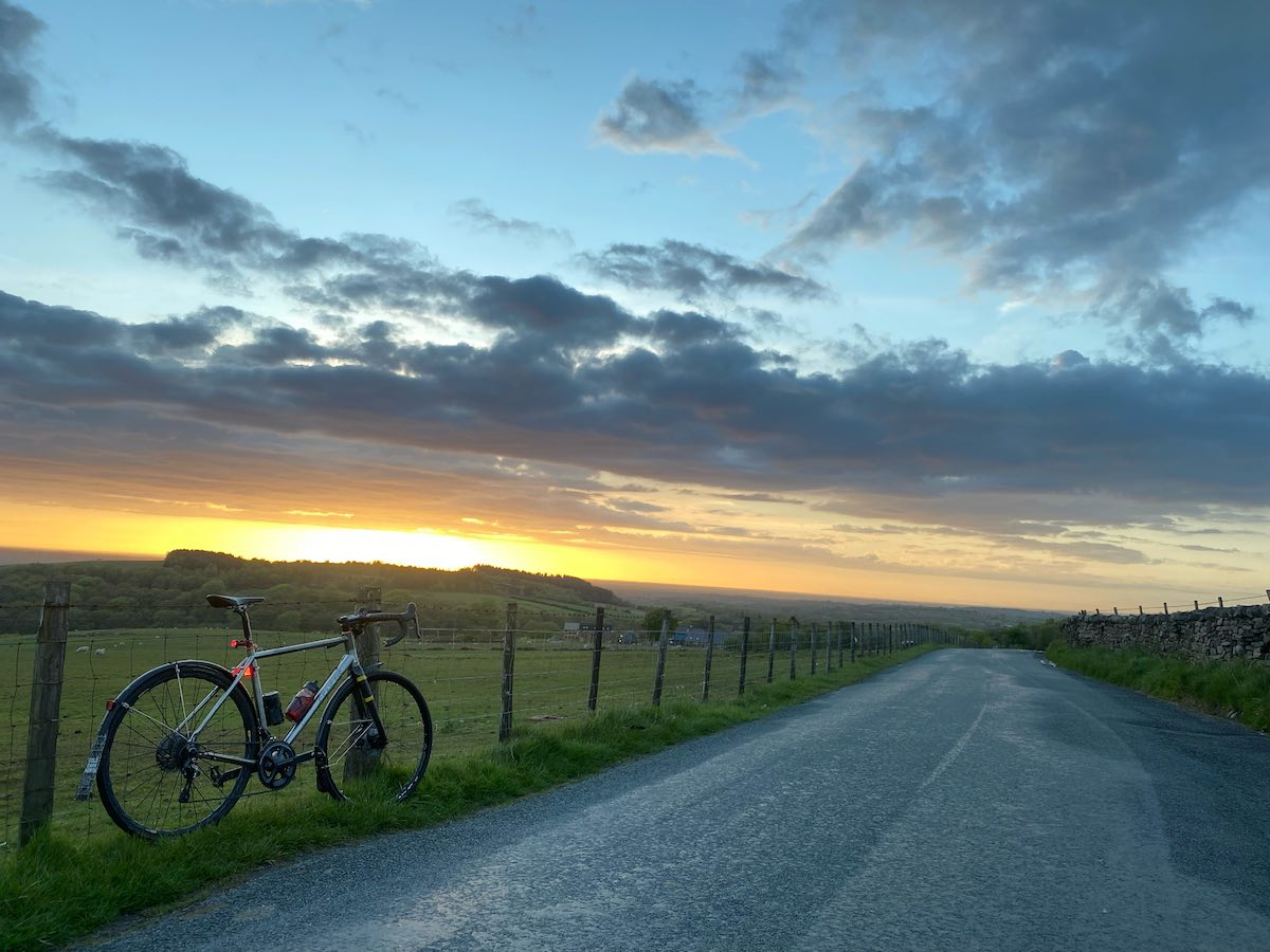 bikerumor pic of the day a bicycle leans against a wire fence along a gravel road next to large green fields, the sun is setting and the clouds and sky are very colorful.
